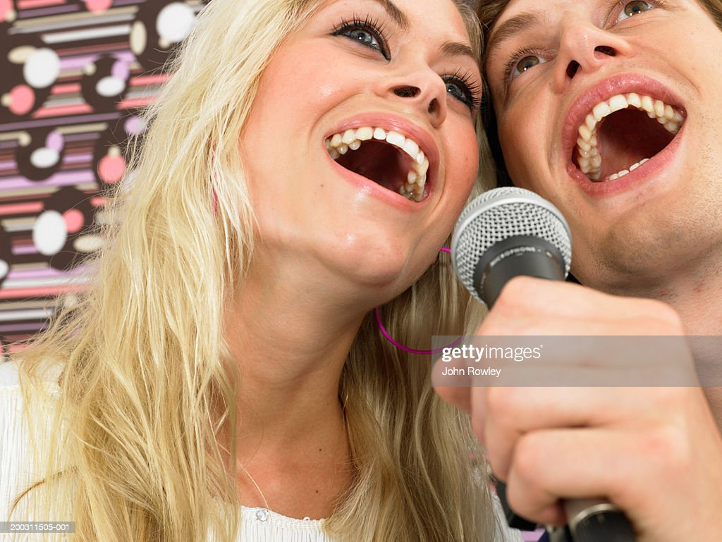 Young woman and man singing into microphone, low angle view : Stock Photo