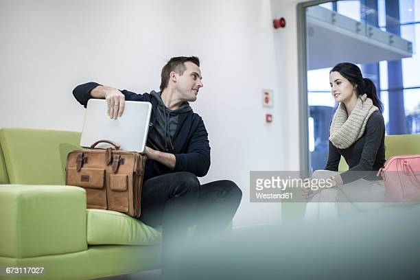 Young woman and man taking out laptop from bag in lobby