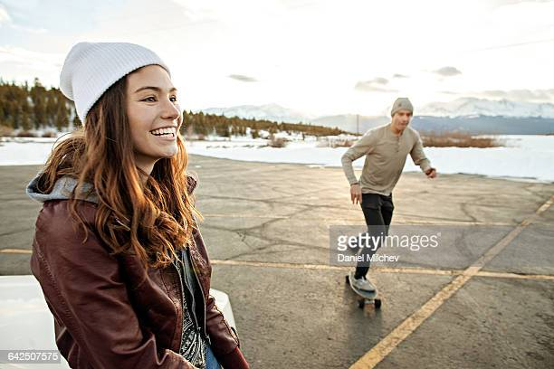 young woman and man with skateboard at sunset - ニット帽 ストックフォトと画像