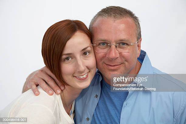 young woman and mature man cheek to cheek, smiling, portrait - compassionate eye foundation stock pictures, royalty-free photos & images