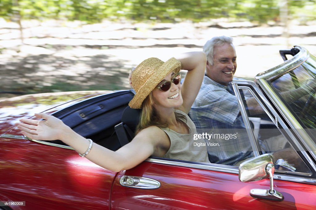 Young Woman and Mature Man Drive in a Convertible Car : Stock Photo