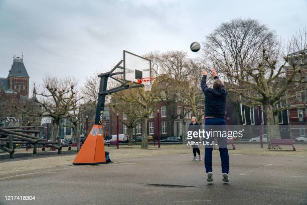 young woman and mature man playing basketball in the park - team sport stock pictures, royalty-free photos & images
