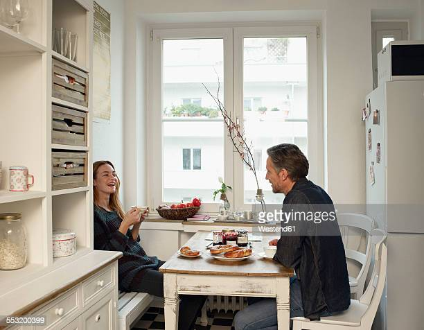 Young woman and mature man sitting in kitchen, having breakfast