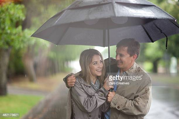 Young woman and mature man walking in rainy park