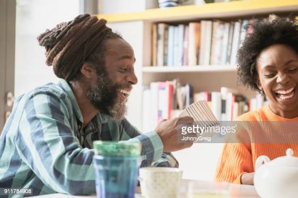 Young woman and mature man with dreadlocks in kitchen laughing