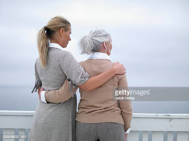 Young woman and mature woman embracing on terrace, looking out to sea