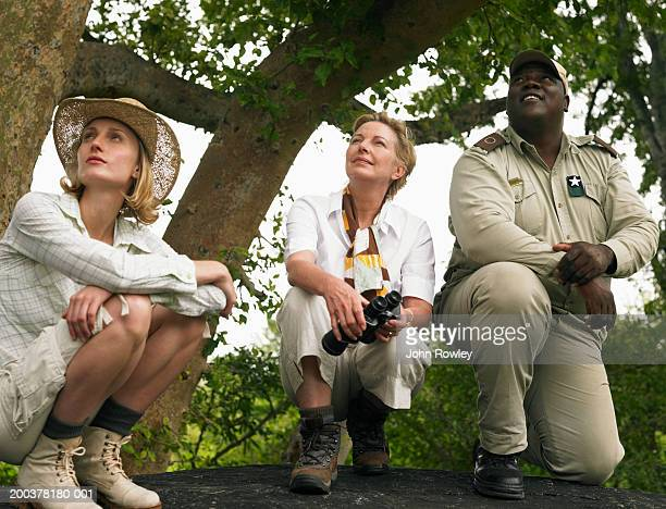 Young woman and mature woman on safari with guide