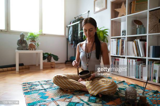 young woman and meditation bell sound therapy at home - rin gong stock pictures, royalty-free photos & images