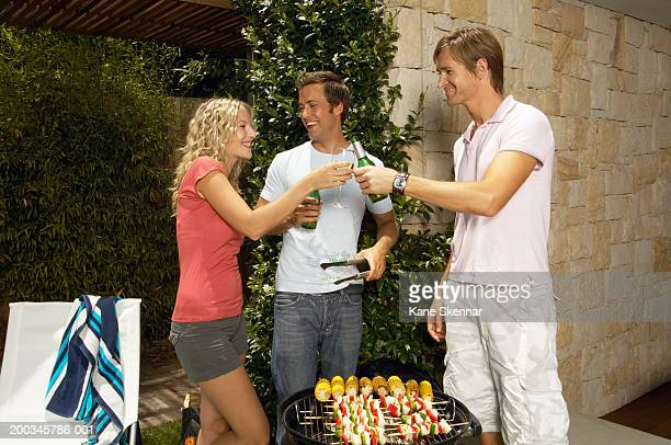 Young woman and men toasting drinks over bbq