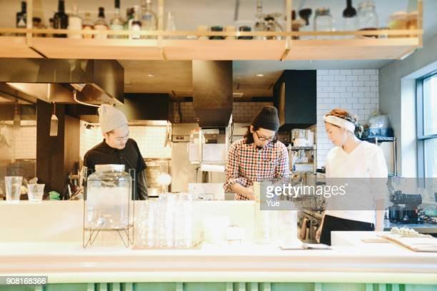 若い女性とカフェで働く男性 - 飲食店 ストックフォトと画像