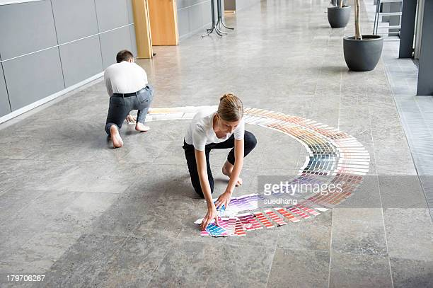 young woman and mid adult man arranging swatches on lobby floor - leanintogether stock pictures, royalty-free photos & images