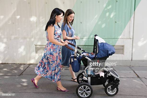 Young woman and mother and pushing baby carriage along street