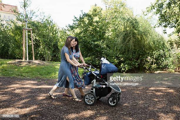 Young woman and mother and pushing baby carriage in park