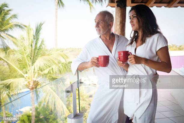 young woman and older man drinking coffee in bathrobes on balcony - sugar daddy stock photos and pictures