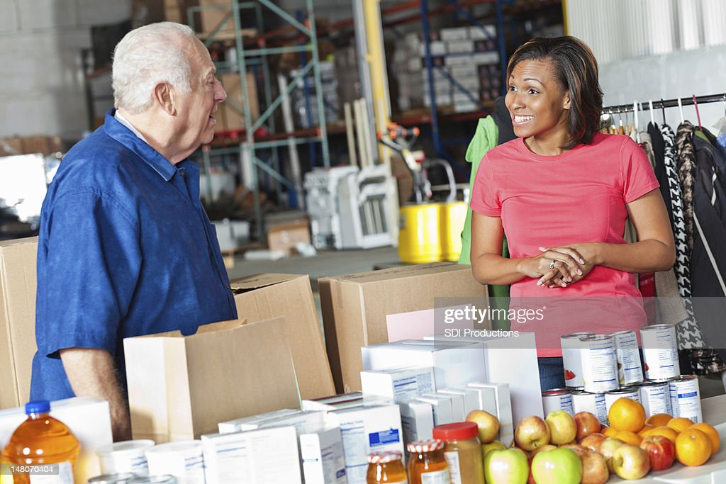 Young woman and older man working at food donation center : Stock Photo
