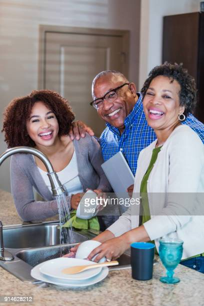 Young woman and parents, washing dishes