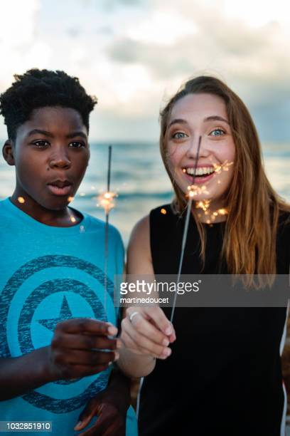 Young woman and preteen boy with sparklers on the beach at dusk