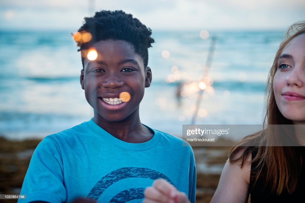 Young woman and preteen boy with sparklers on the beach at dusk : Stock Photo