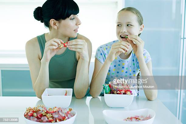 young woman and preteen girl eating candy - bowl of candy stock photos and pictures