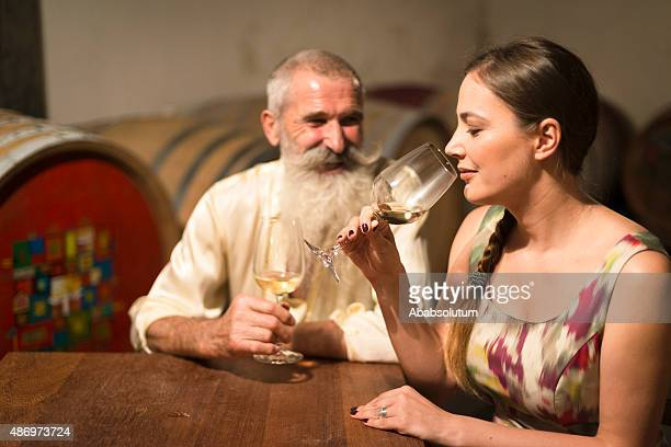 Young Woman and Senior Man Tasting White Wine, Cellar, Europe