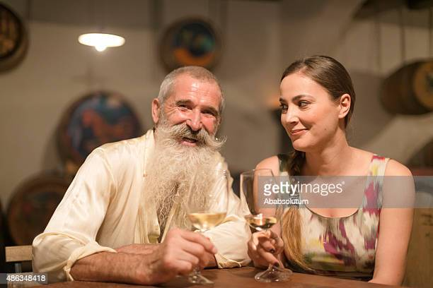 young woman and senior man toasting, white wine, cellar, europe - old man young woman stock photos and pictures