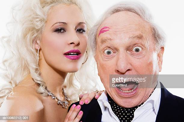 young woman and senior man with lipstick mark on forehead, portrait - may december romance stock photos and pictures