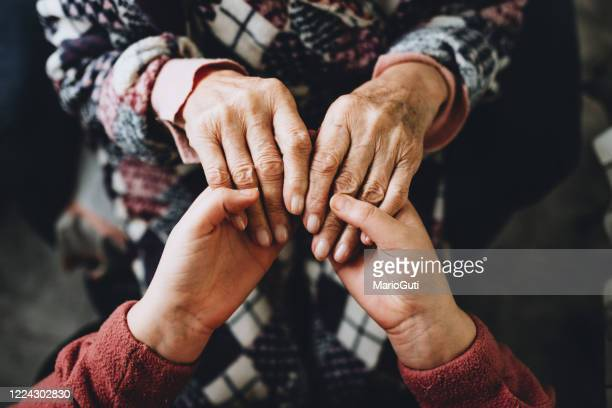 young woman and senior woman holding hands - forgiveness stock pictures, royalty-free photos & images