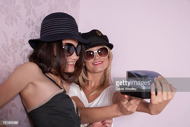 Young woman and teenage girl (16-17) dressed up, photographing themselves