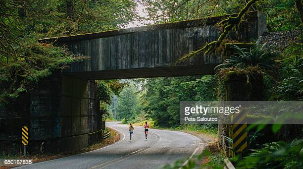 young woman and teenage girl running along rural road, rear view - kitsap county washington state stock pictures, royalty-free photos & images