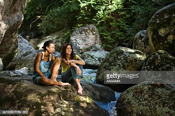 young woman and teenage girl (16-17 years) sitting on rock by waterfall in forest, smiling - 16 17 years stock pictures, royalty-free photos & images