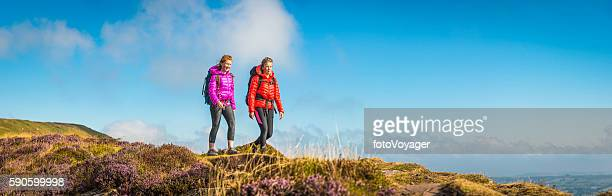 Young woman and teenage hiker walking picturesque summer mountain panorama