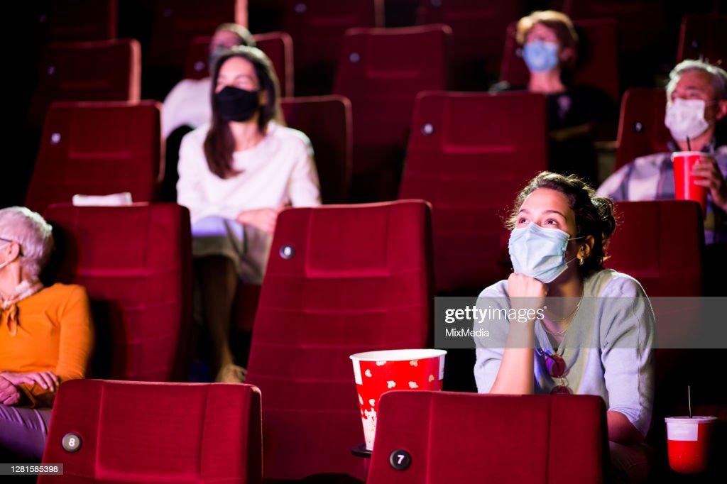 Jonge vrouw en de andere toeschouwers die beschermende gezichtsmaskers bij de bioskoop dragen : Stockfoto