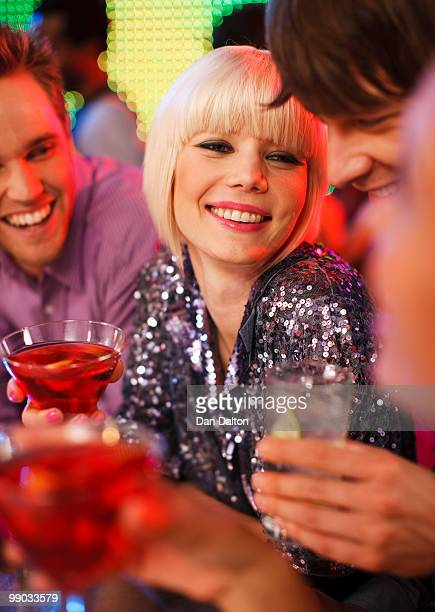 Young woman and two male friends drinking in a bar