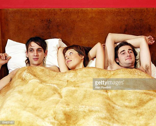 young woman and two men lying in bed - halbbekleidet stock-fotos und bilder