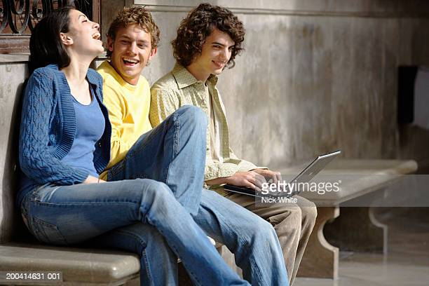 Young woman and two young men sitting on bench, smiling