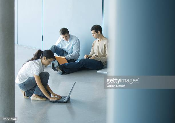 Young woman and two young men using laptops on floor