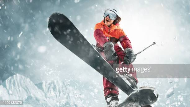 young woman and winter sport - she is skiing against white alps mountains - freestyle skiing stock pictures, royalty-free photos & images