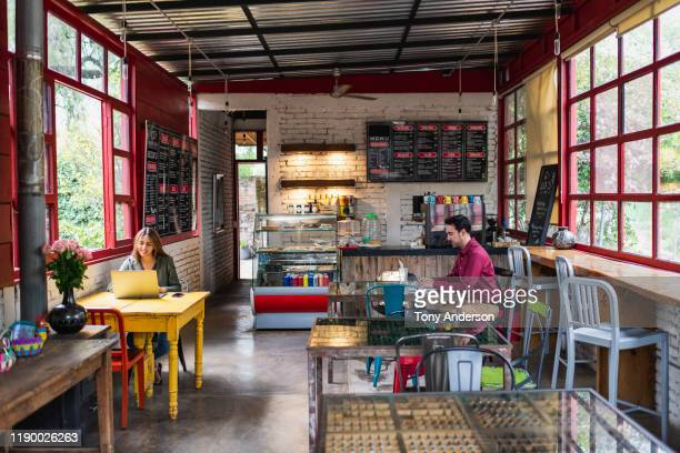 young woman and young man working with laptops and phones in coffee shop - メキシコ 街 ストックフォトと画像