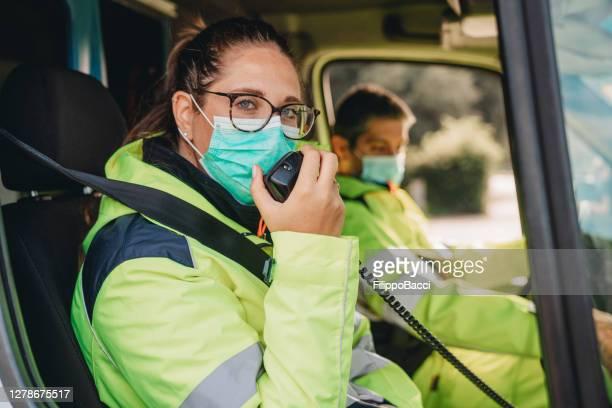 young woman answering a call in an ambulance - rádio aparelhagem de áudio imagens e fotografias de stock
