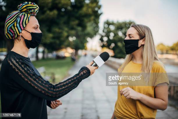 young woman answering to female journalists on the street during coronavirus pandemic - live event stock pictures, royalty-free photos & images