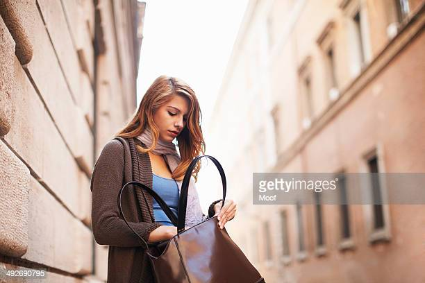 Young woman anxiously searching her shoulder bag