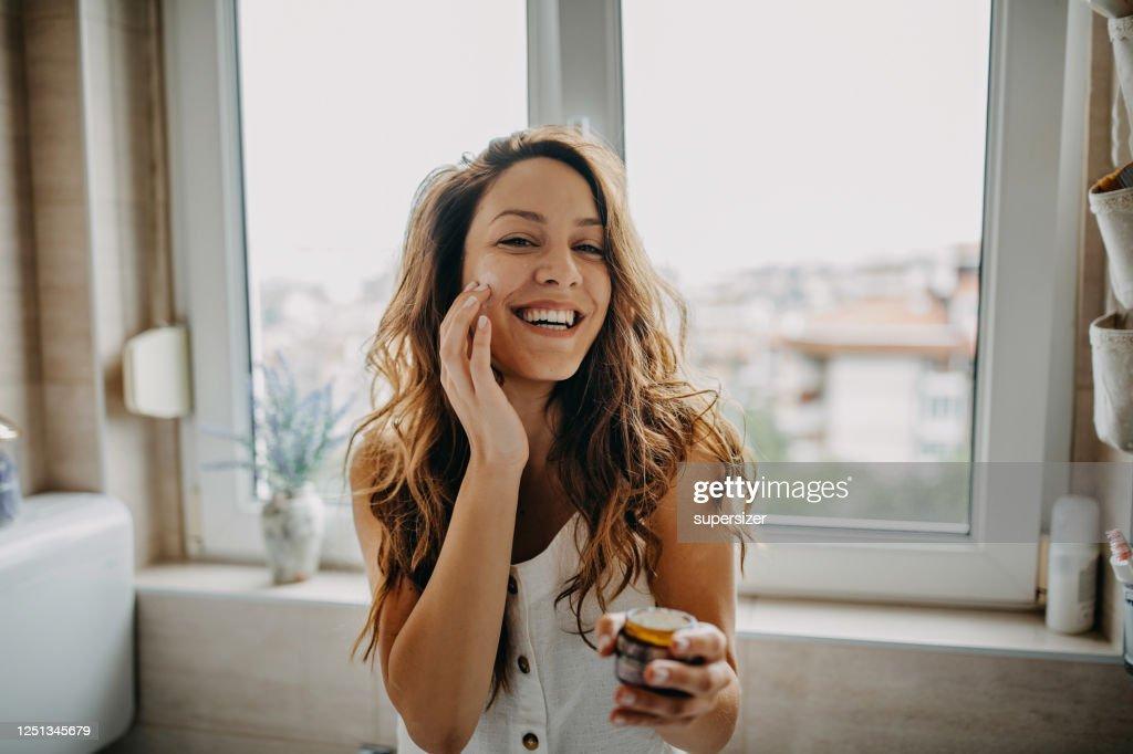 若い女性はフェイシャルクリームを適用します : ストックフォト