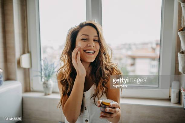 young woman applies facial cream - human skin stock pictures, royalty-free photos & images