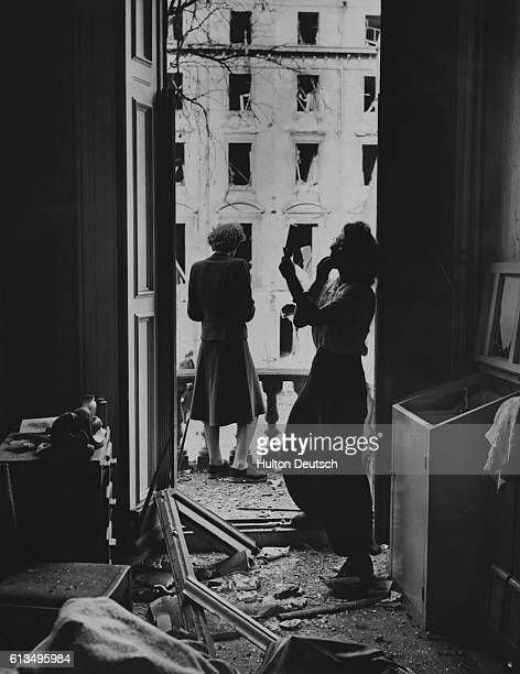 A young woman applies her makeup as usual as another day unfolds in a bombdamaged block of flats in London England October 1940