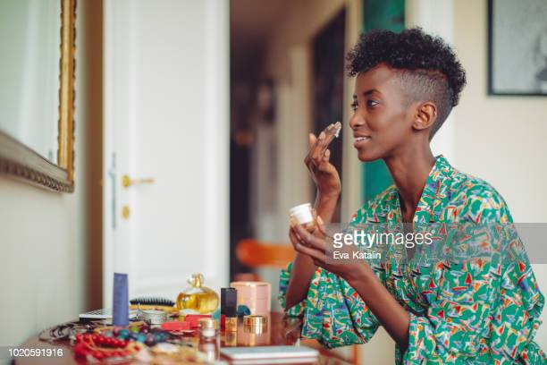 young woman applying a moisturiser in the morning - moisturiser stock pictures, royalty-free photos & images