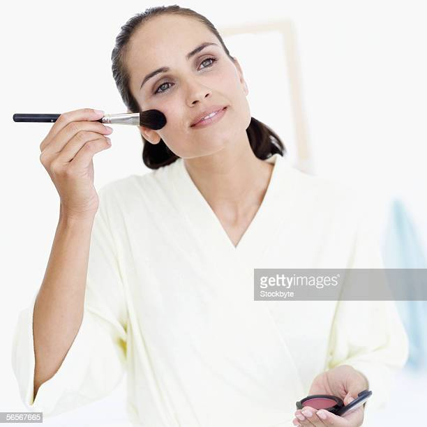 young woman applying blush with a brush - rosy cheeks stock pictures, royalty-free photos & images