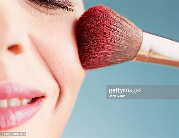 Young woman applying blusher, close-up of cheek