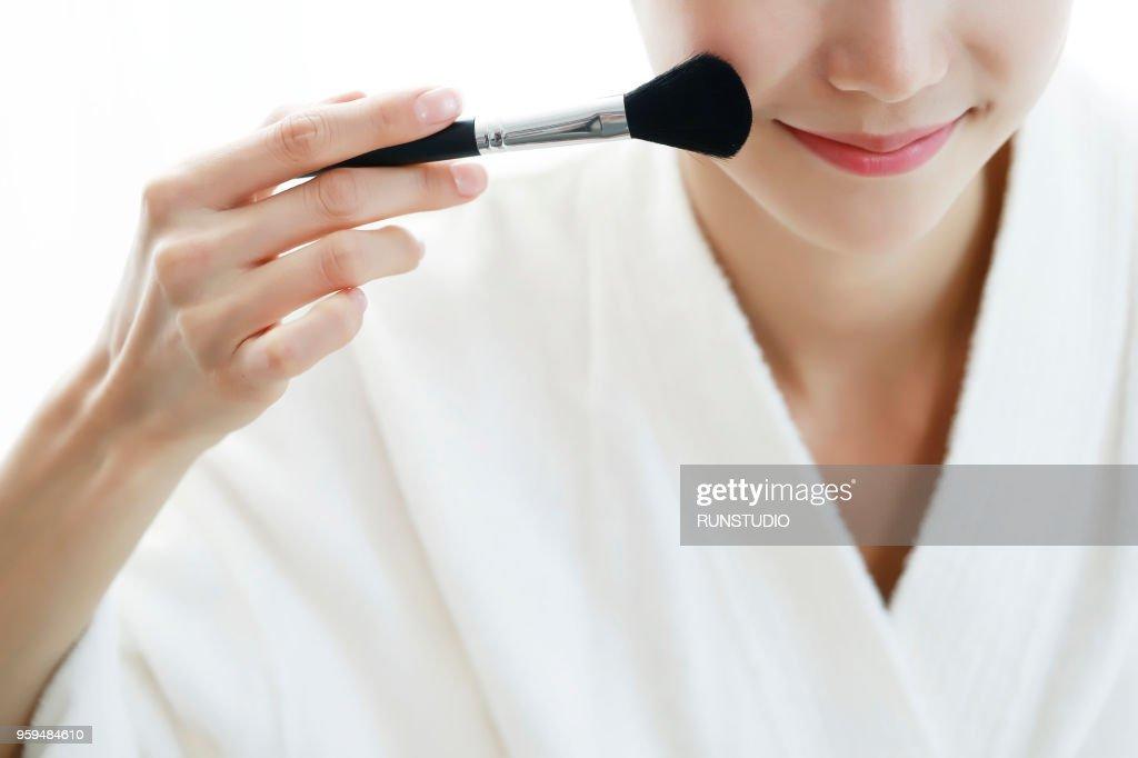 Young woman applying blusher, close-up of cheek : Stock-Foto