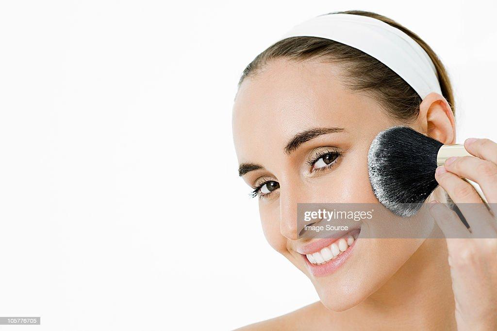Young woman applying blusher : Stock Photo
