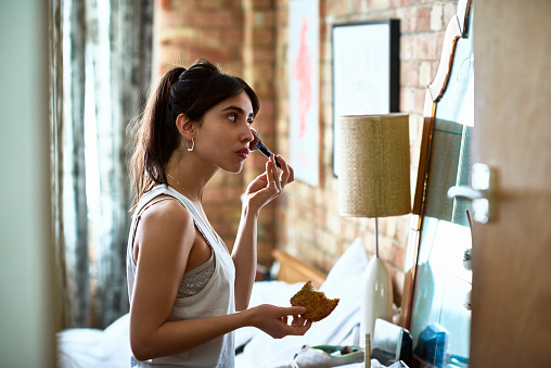 Young woman applying blusher with make up and holding toast - gettyimageskorea